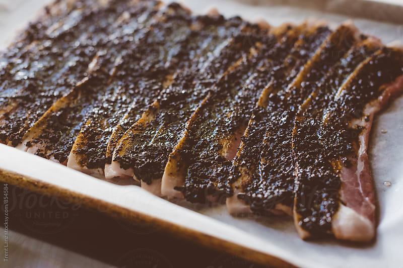 Close-up of smoked bacon slices covered with coffee grounds by Trent Lanz for Stocksy United