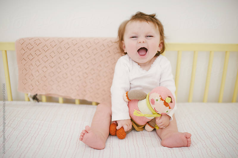 cute baby girl laughing in crib with doll by Kristin Rogers Photography for Stocksy United