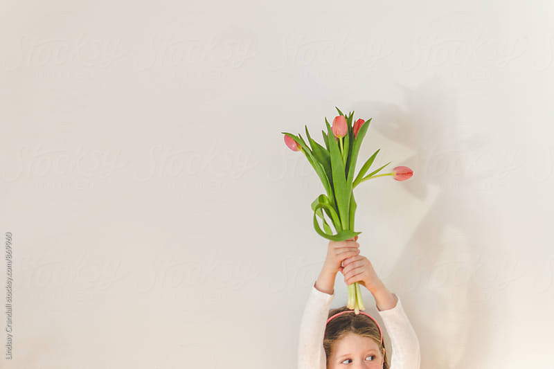 Young child holding tulips overhead by Lindsay Crandall for Stocksy United