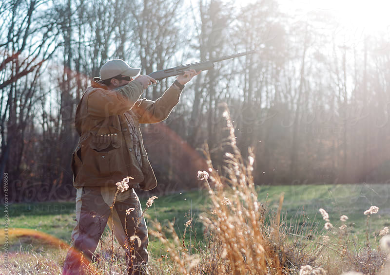 Man aiming shotgun while hunting in field by Matthew Spaulding for Stocksy United