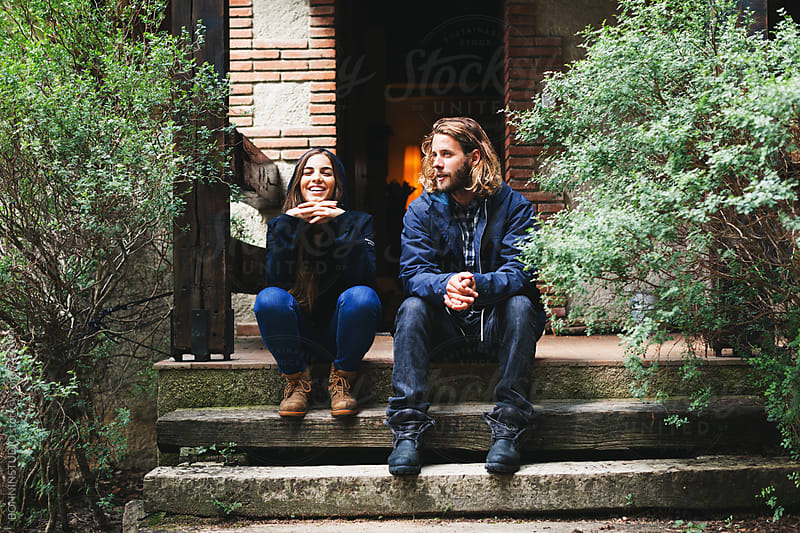 Young couple sitting on the stairs in front of the rural house. by BONNINSTUDIO for Stocksy United