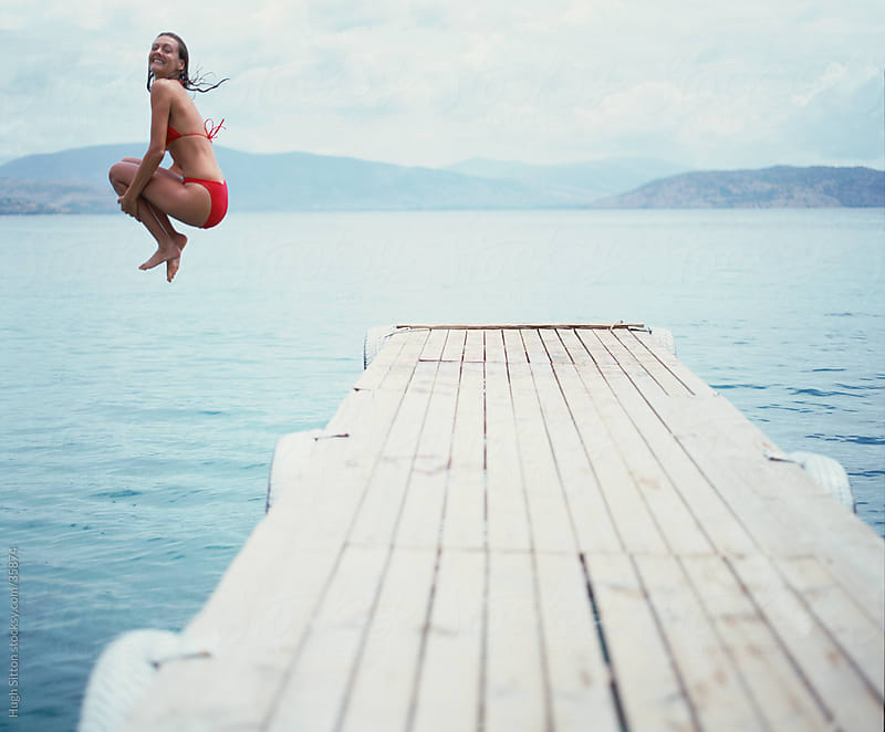 Woman jumping off the end of jetty into the sea. by Hugh Sitton for Stocksy United