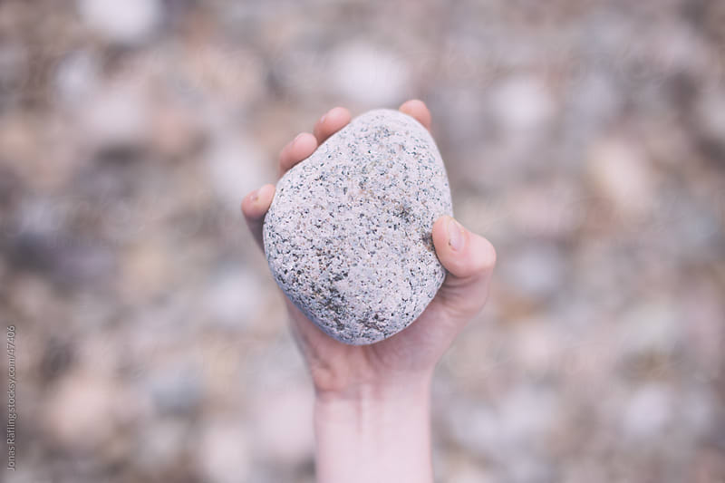 A hand holding a stone above a lot of stones by Jonas Räfling for Stocksy United