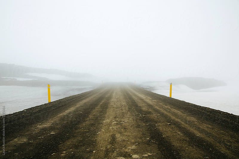 Misty Dirt Road Through Snowy Mountains by Laura Austin for Stocksy United