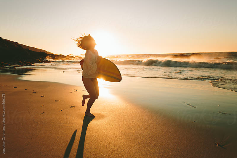 Young woman surfer with surfboard running on beach at sunset by Jonathan Caramanus for Stocksy United