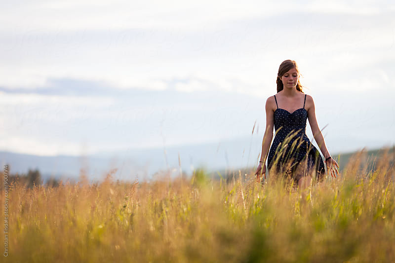 Beautiful young girl walking in long grass field  by Christian Tisdale for Stocksy United