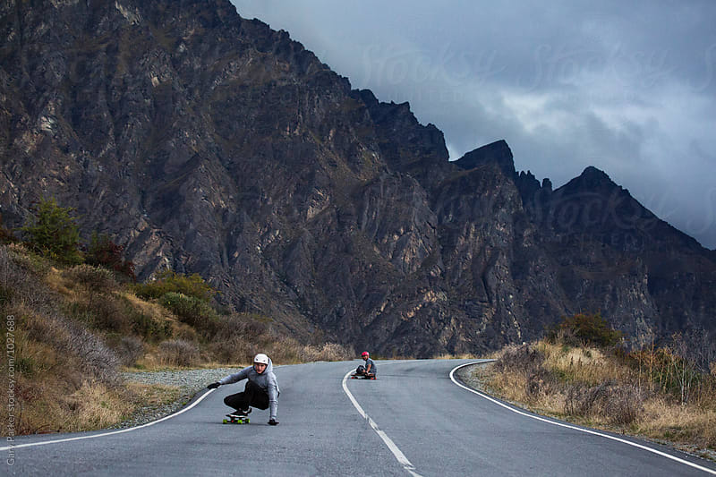 Skateboarders bombing a big hill in New Zealand by Gary Parker for Stocksy United