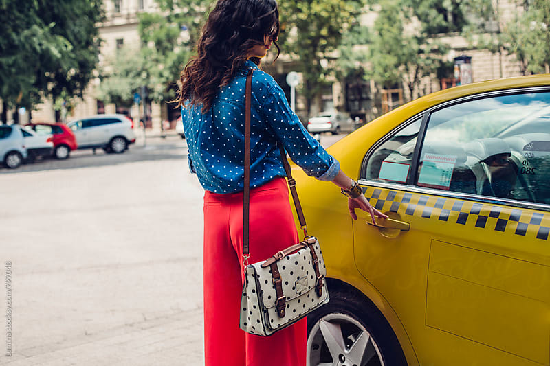 Woman Opens a Taxi Door  by Lumina for Stocksy United