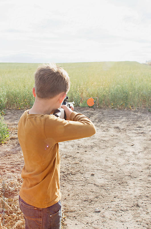boy aiming bb gun at target in rural field by Tana Teel for Stocksy United