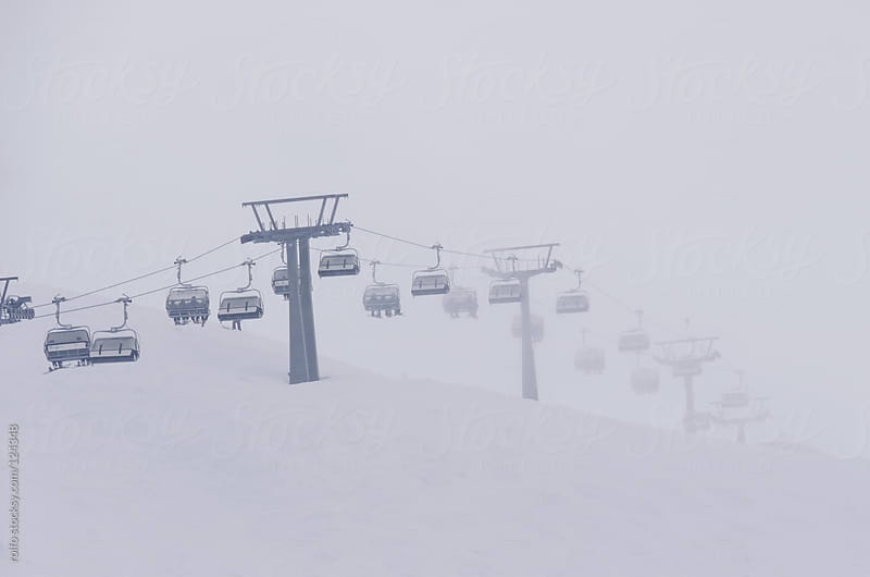 Ski lift on a cold wintry snowy mountain by rolfo for Stocksy United