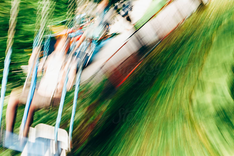 Unrecognizable people riding on a swing carousel in amusement park by Ilya for Stocksy United