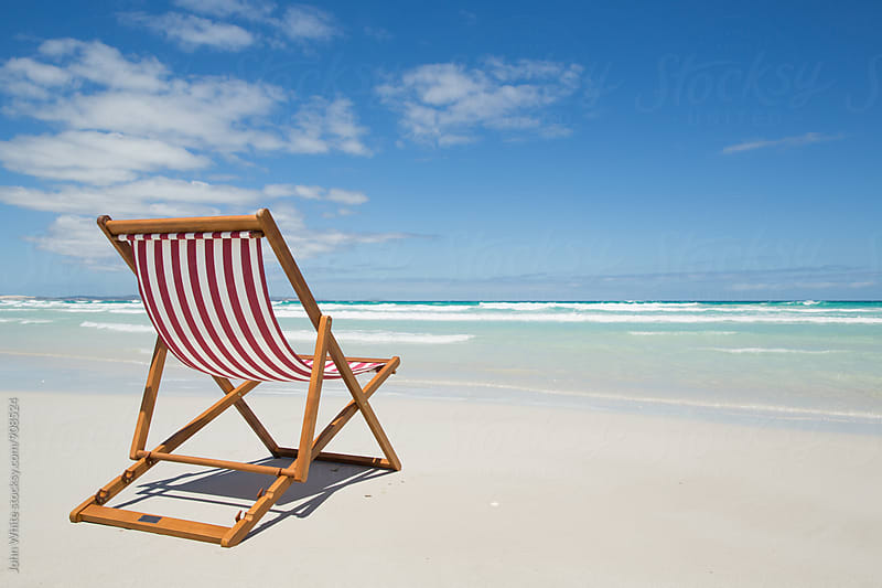 Deck chair on a beach. by John White for Stocksy United