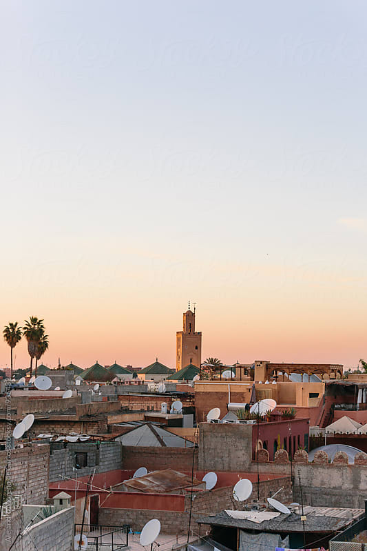 Minaret of a mosque over rooftops at sunset with copy space by Alejandro Moreno de Carlos for Stocksy United