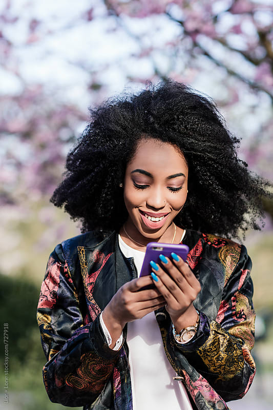 Young black woman smiling while texting on her phone by Lior + Lone for Stocksy United