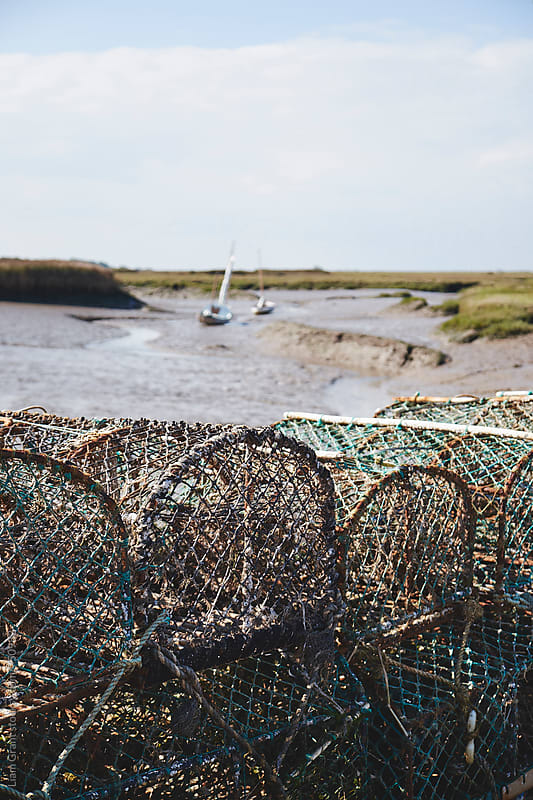 Lobster pots and sailing boats at low tide. Brancaster Staithe, Norfolk, UK. by Liam Grant for Stocksy United