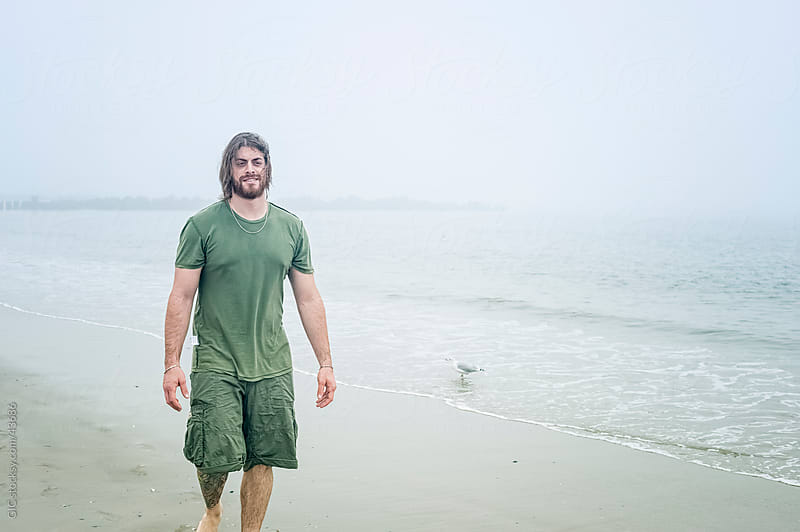 Young man walking on the beach by GIC for Stocksy United