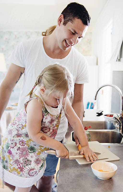 daughter and father cooking dinner by Andreas Gradin for Stocksy United