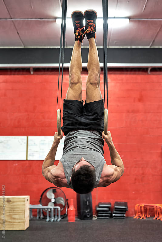 Man working out on rings in a gym by Guille Faingold for Stocksy United