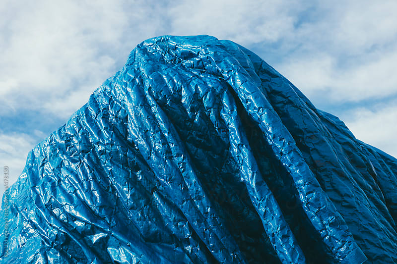 Blue tarpaulin covering pile of commercial fishing equipment by Paul Edmondson for Stocksy United