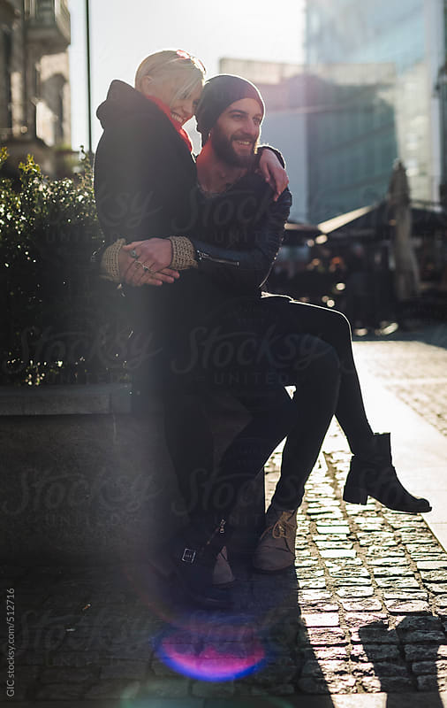 Young couple sitting and having fun in the city by GIC for Stocksy United