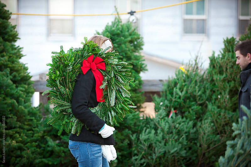 Tree Lot: Woman Carrying a Christmas Wreath by Sean Locke for Stocksy United