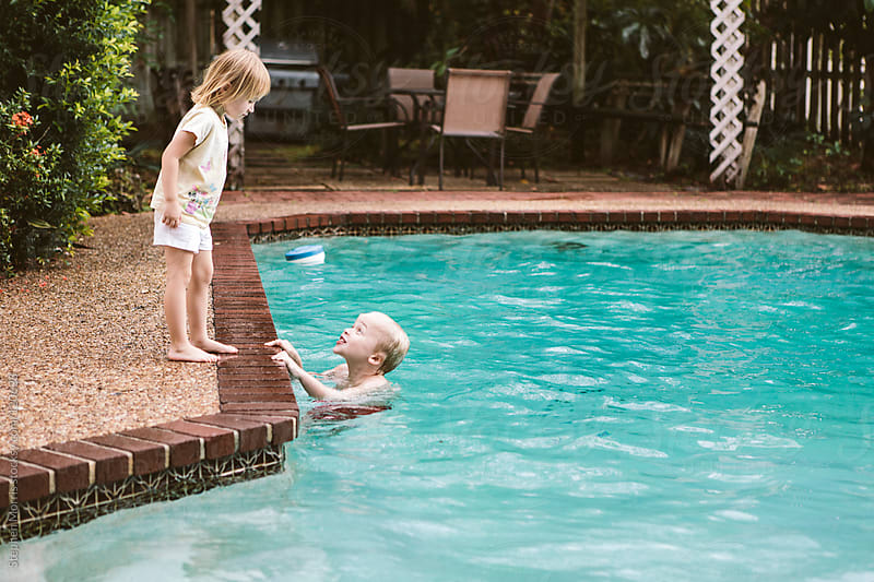 Brother and sister by pool by Stephen Morris for Stocksy United