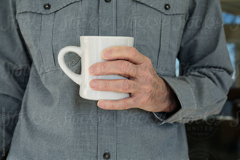 Man's hand holding a white coffee mug by David Smart for Stocksy United