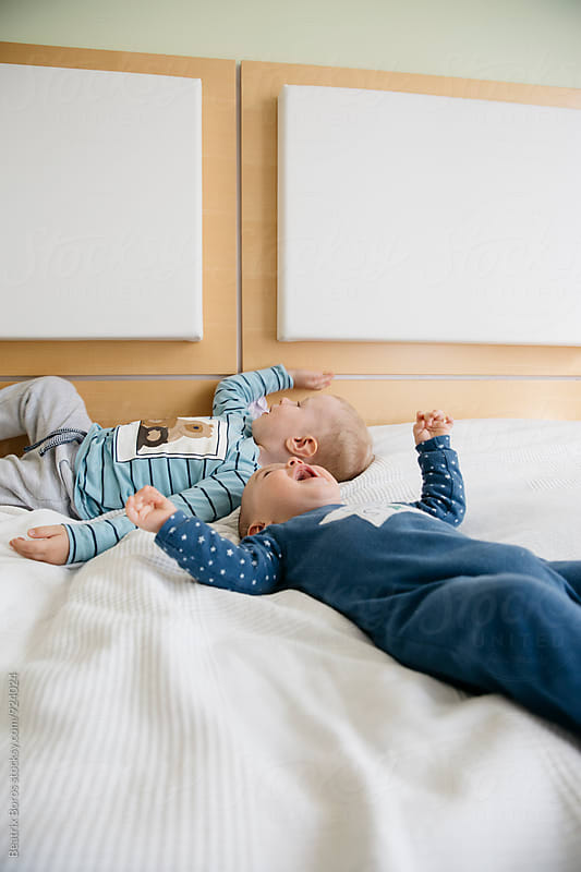 Kids lying on bed by Beatrix Boros for Stocksy United