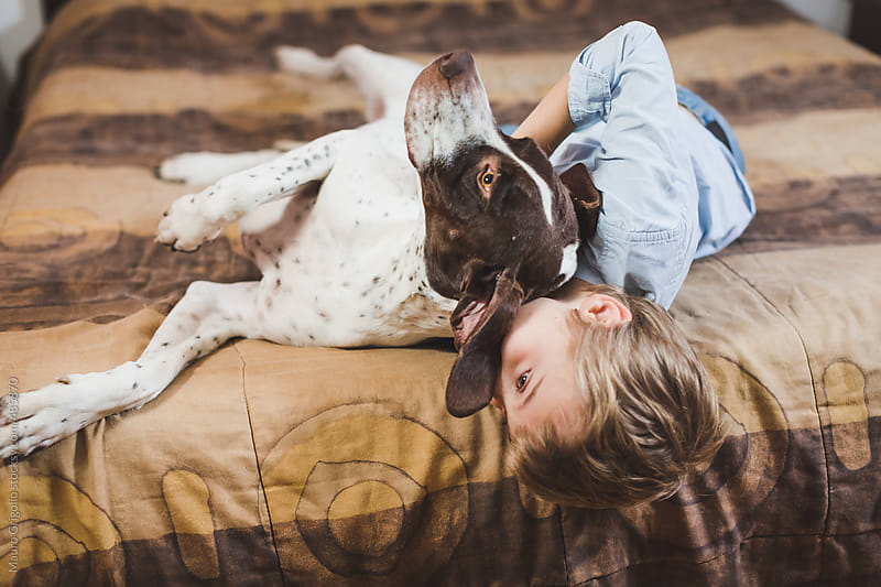 Young boy playing with his dog by Mauro Grigollo for Stocksy United