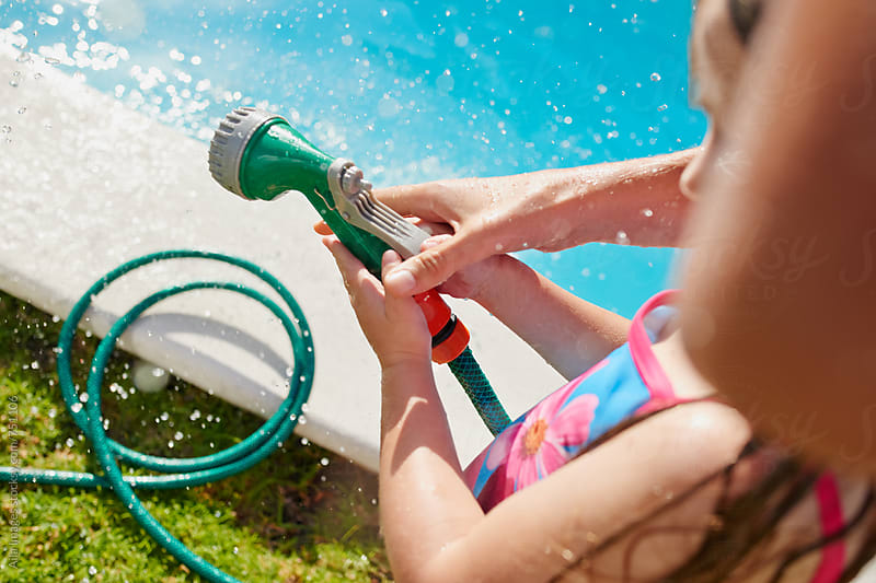 family having a water fight  by Aila Images for Stocksy United
