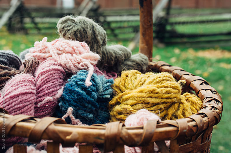 Colorful yarns of naturally dyed wool in a basket by Gabriel (Gabi) Bucataru for Stocksy United
