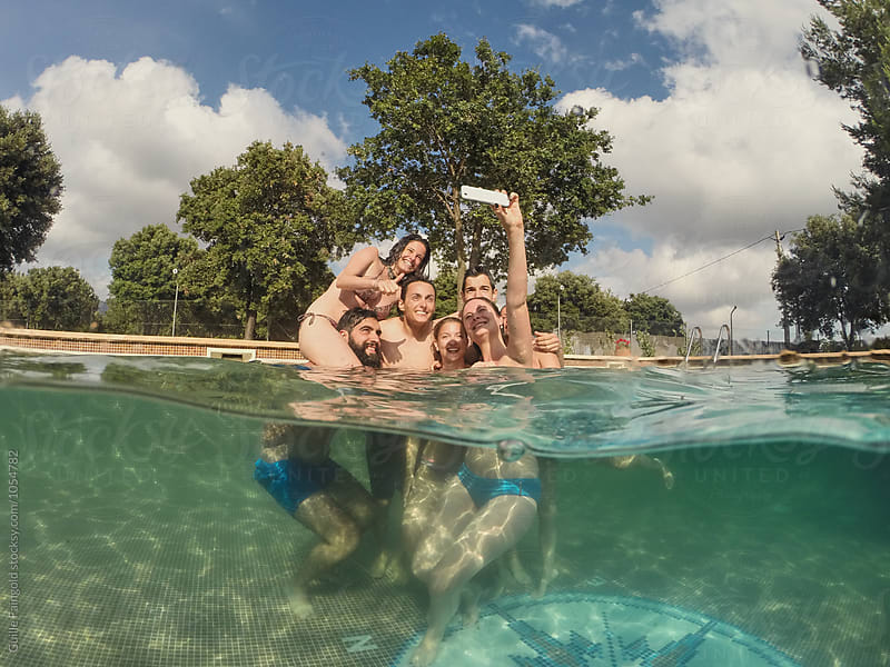 Smiling friends in pool making selfie using cell by Guille Faingold for Stocksy United