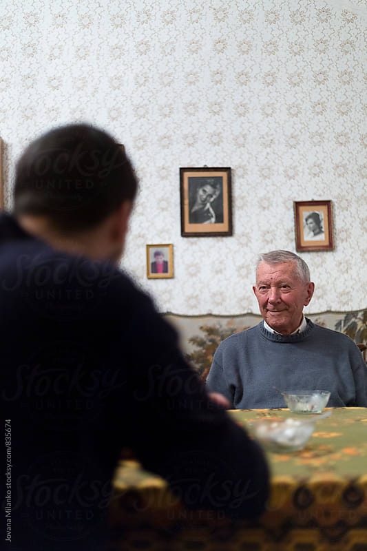 Two men  sitting at the table across of each other  by Jovana Milanko for Stocksy United