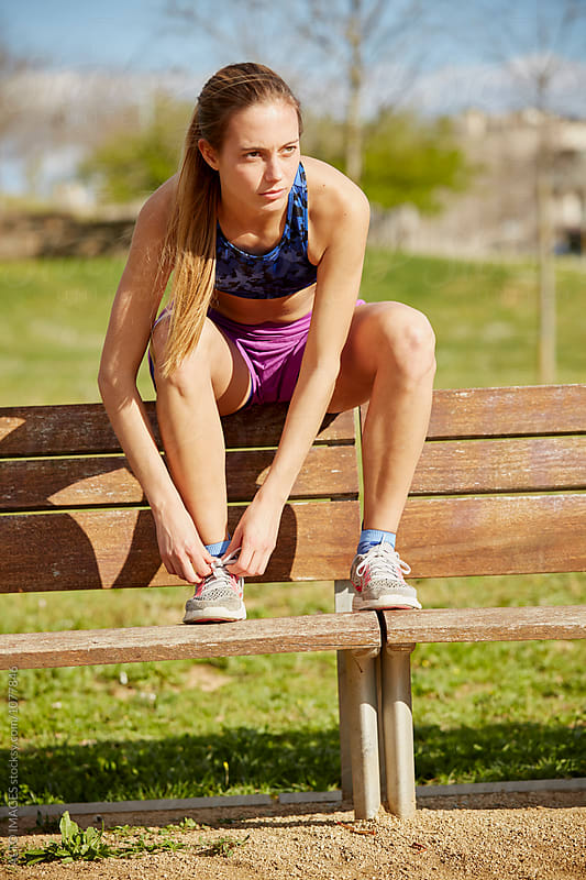 Sporty Woman Tying Shoelace On Bench In Park by ALTO IMAGES for Stocksy United