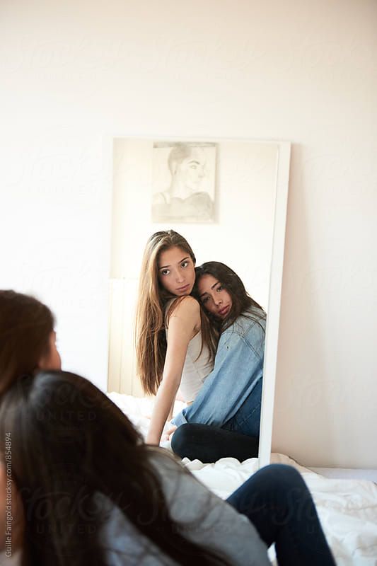 Two girlfriends looking in the mirror while hugging by Guille Faingold for Stocksy United