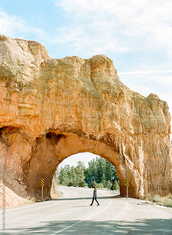 young woman walking across road under rock arch by Daniel Kim Photography for Stocksy United