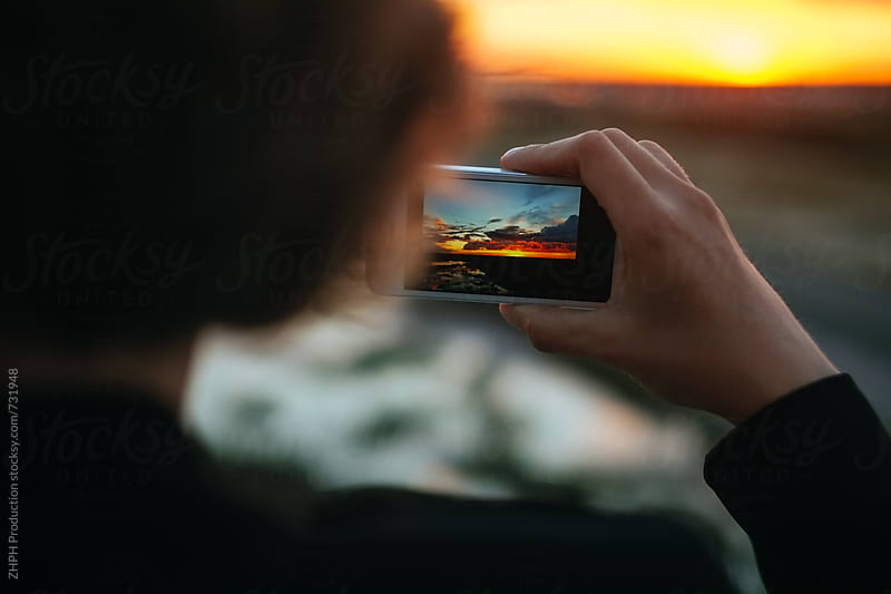 Shooting a sunset with smartphone by Artem Zhushman for Stocksy United