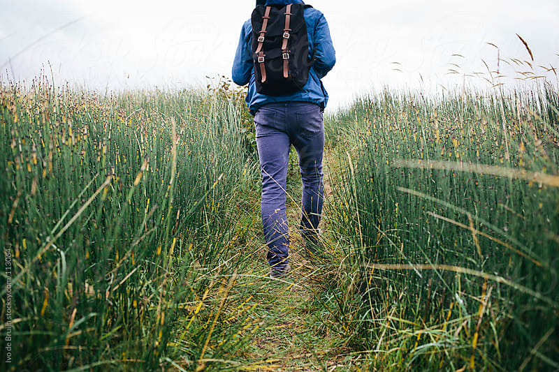 Man with a backpack walking on a path with high grass on both si by Ivo de Bruijn for Stocksy United