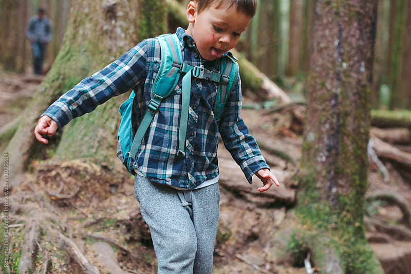 Young caucasian boy hiking in forest by Rob and Julia Campbell for Stocksy United