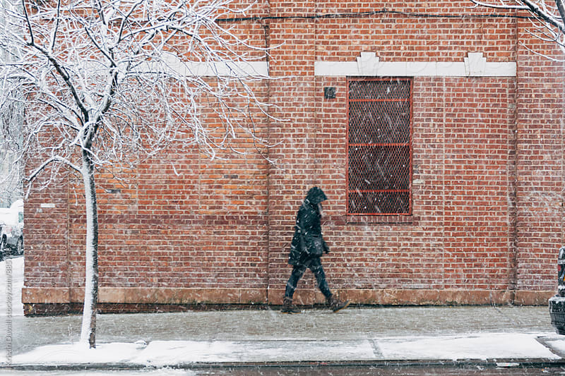 Blurred pedestrian walking through snowstorm. New York City. by Kristin Duvall for Stocksy United