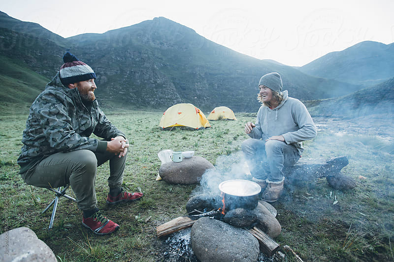 hikers around a camp fire at dawn by Micky Wiswedel for Stocksy United