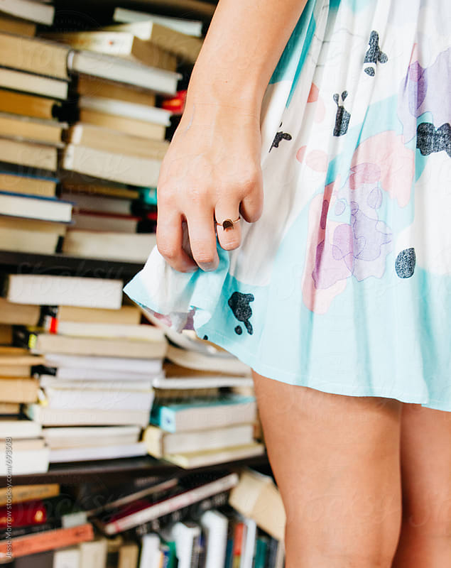 young female wearing light blue dress standing in front of book shelf by Jesse Morrow for Stocksy United