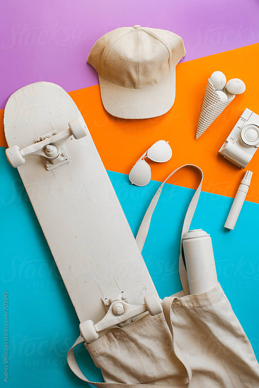 Content of skateboarder/teenager bag with various objects  on blue orange and purple background. by Audrey Shtecinjo for Stocksy United
