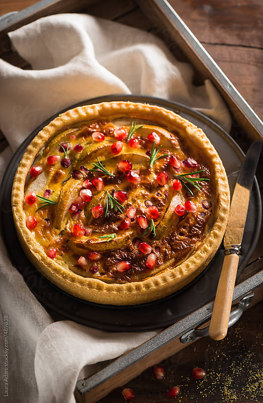 Savory tart with pear, cheese and pomegranate by Laura Adani for Stocksy United