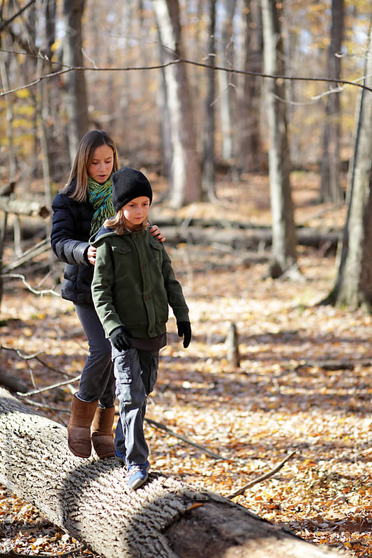 Siblings Walking On A Log During An Autumn Hike by ALICIA BOCK for Stocksy United