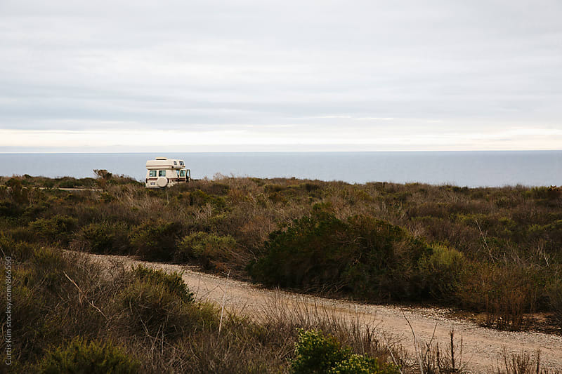 RV camper parked surrounded by nature and ocean by Curtis Kim for Stocksy United