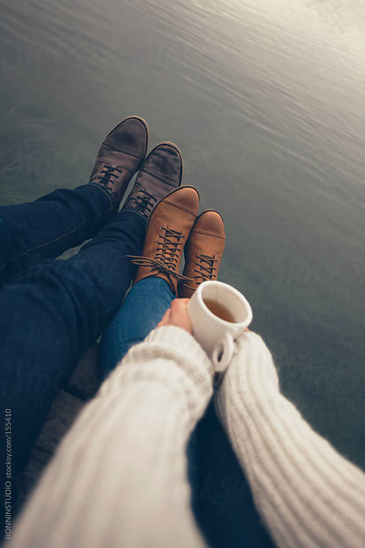 Closeup of legs of couple relaxing at the lakeshore with one tea cup. by BONNINSTUDIO for Stocksy United