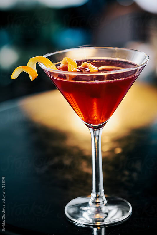 Cosmopolitan cocktail with orange garnish by Borislav Zhuykov for Stocksy United