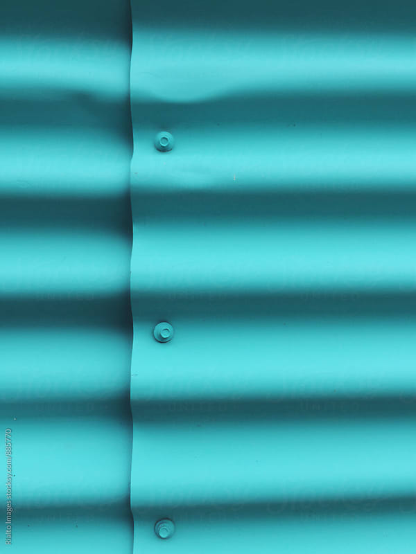 Turquoise painted metal wall of warehouse, close up by Paul Edmondson for Stocksy United