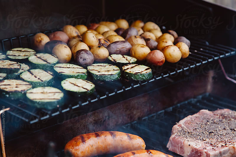 Grilling a summer meal on a barbecue. by Carey Shaw for Stocksy United